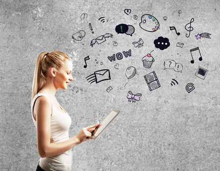 online education: young woman standing against concrete wall and using  touch pad