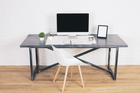 designer chair: Designer desk with blank computer screen, picture frame and modern white chair next to it on wooden floor and brick background. Mock up Stock Photo