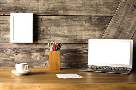 stationery items: Closeup of creative wooden designer desktop with blank white laptop screen, picture frame, coffee cup and stationery items. Mock up