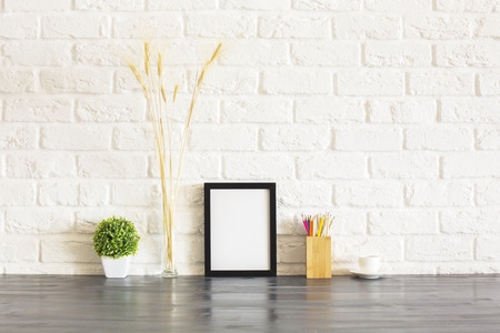 pencil holder: Blank picture frame, pencil holder, plant, wheat spikes and coffee cup on wooden desktop and white brick wall background. Mock Stock Photo