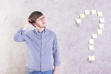 wall paper: Thoughtful caucasian male standing next to sticker question mark glued onto concrete wall and scratching head Stock Photo