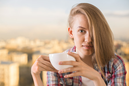 swept: Gorgeous european woman with side swept hair drinking coffee on blurry city background Stock Photo