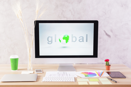 stationery items: Global network concept with computer monitor on creative desktop with coffee cup, electronic devices and stationery items Stock Photo