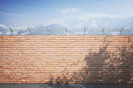 prison wall: Red brick prison wall with shadows and snowy mountains view. Mock up, 3D Rendering