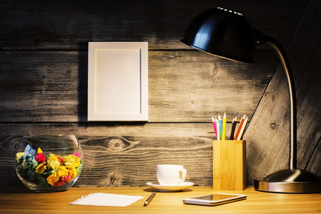 lit lamp: Front view of creative hipster desktop with lit lamp, picture frame, coffee cup, smart phone and stationery items. Mock up