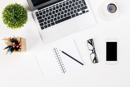 Top view of white office desktop with laptop keyboard, plant, coffee cup, glasses, smartphone and stationery items. Mock up