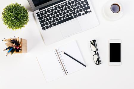 papeleria: Vista superior de la mesa de la oficina blanco con un teclado portátil, planta, la taza de café, vasos, smartphone y artículos de papelería. Bosquejo