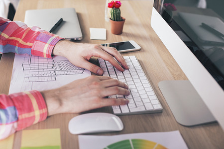 Side view of male hands using computer keyboard on wooden desktop with construction sketch, computer monitor, smart phone, cactus and other items