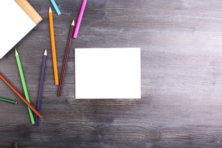 up view: Top view of dark wooden desktop with blank square piece of paper and colorful pencils. Mock up Stock Photo