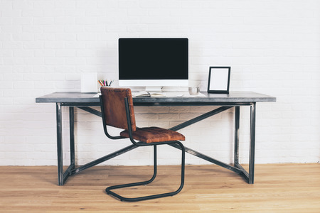 Front View Of Designer Desk With Blank Computer Display Frames And Other Items Brown