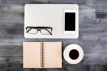 up view: Dark wooden desktop with neatly organized laptop, coffee cup, notepad, blank smart phone and glasses. Top view, Mock up Stock Photo