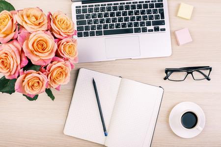 Bovenaanzicht van het bureaublad van creatieve vrouw met open kladblok, potlood, glazen, kopje koffie, rozen en laptop toetsenbord
