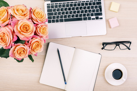 Top view of creative  womans desktop with open notepad, pencil, glasses, coffee cup, roses and laptop keyboard
