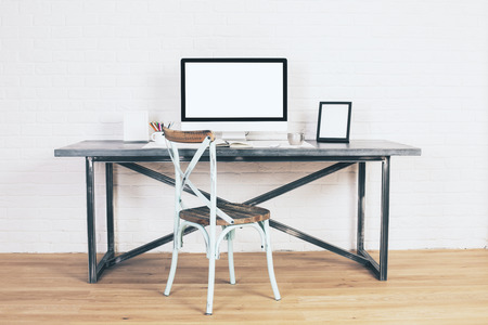 designer chair: Creative antique chair next to designer desk with blank white computer screen and picture frames. Mock up Stock Photo