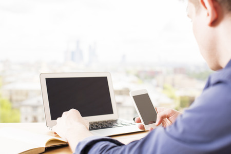 Young man sitting at desk and using laptop computer and smart phone with blank screens on blurry city background. Mock up