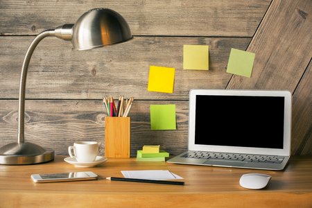 Creative hipster desktop with blank laptop screen, lamp, coffee cup, smartphone and stationery items. Mock up Stock Photo