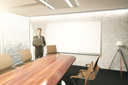 table and chairs: Businessman using laptop in conference room interior with table, chairs, floor lamp and blank whiteboard on brick wall. Mock up, 3D Rendering