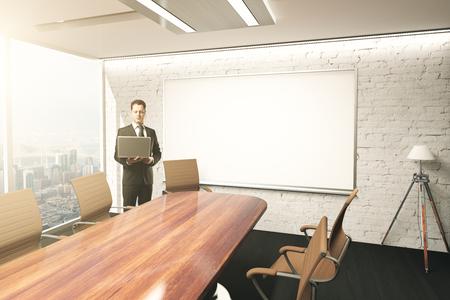 El hombre de negocios usando la computadora portátil en el interior de la sala de conferencias con mesa, sillas, lámpara de pie y pizarra en blanco en la pared de ladrillo. Maqueta, 3D