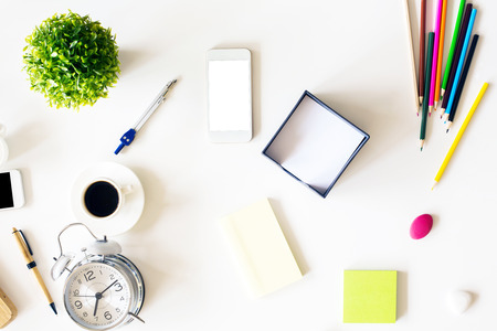 stationery items: Top view of messy office desktop with blank white smart phone, plant, alarm clock and various stationery items. Mock up