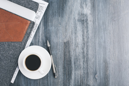 computer case: Top view of dark wooden desktop with coffee cup and saucer, pen and notebook cover. Mock up