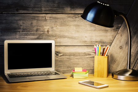 lit lamp: Closeup of creative hipster desktop with blank laptop screen, lit lamp, smartphone and stationery items on wooden background. Mock up Stock Photo