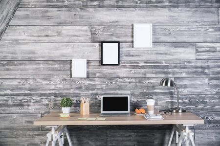 Front view of modern designer workspace with blank laptop, coffee, lamp, various stationery items and three blank picture frames hanging above on wooden wall. Mock up