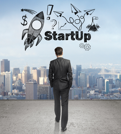 towards: Start up concept with rocket ship sketch and businessman walking towards city on concrete ground Stock Photo