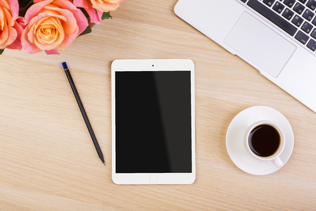 blank screen: Top view of creative womans desktop with roses, blank tablet screen, coffee cup, pencil and laptop keyboard. Mock up Stock Photo