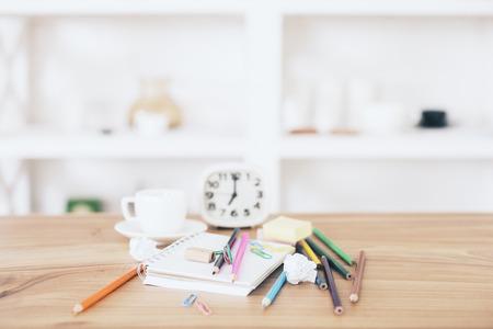 Messy kantoor bureaublad met kantoorartikelen, klok en koffiekopje met onscherpe planken op de achtergrond Stockfoto
