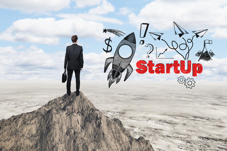 back up: Start up concept with rocket ship sketch and businessman looking at desert from mountain top Stock Photo