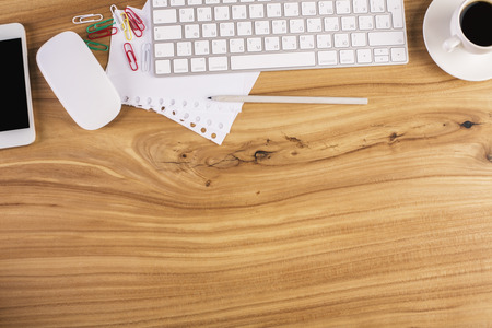 Top view of wooden office desktop with smartphone, computer mouse and keyboard, coffee cup and stationery items. Mock up Stock Photo