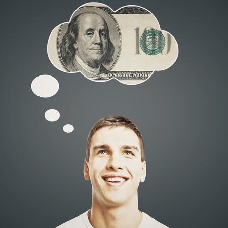 personas pensando: Hombre joven hermoso que piensa en el dinero en el fondo gris oscuro