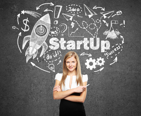 woman looking up: Startup concept with confident young businesswoman and rocket ship sketch on concrete background