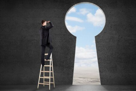 key to success: Success concept with businessman on ladder looking through keyhole shaped door with clear sky view in concrete room Stock Photo