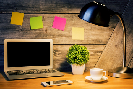 lit lamp: Creative designer desktop with blank laptop screen, lit lamp, colorful stickers, plant, smart phone and coffee cup. Mock up