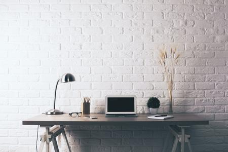 Vista frontal de la creatividad de diseño de escritorio de madera con la computadora portátil en blanco, plantas decorativas, lámpara de mesa, vasos y artículos de papelería en el fondo blanco de la pared de ladrillo. Bosquejo
