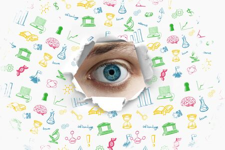 eyes closeup: Education concept with blue eye looking through hole in wallpaper with educational icons Stock Photo