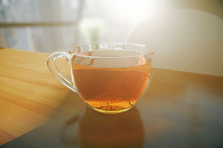 tea cup: Wooden desktop with transparent tea cup on blurry background with sunlight. Closeup, 3D Rendering