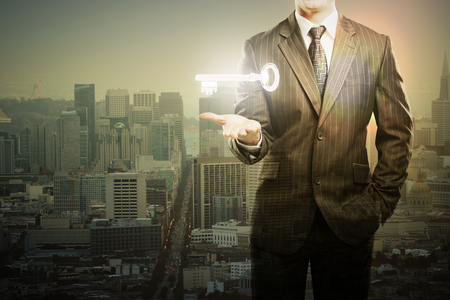 levitating: Businessman holding levitating key in city with setting sun. Double exposure