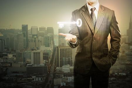 llave de sol: El hombre de negocios que sostiene levitando clave en la ciudad con el establecimiento de sol. Exposicion doble Foto de archivo