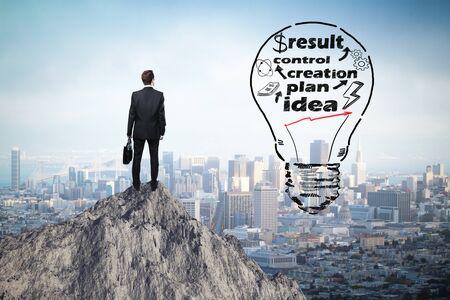 concept idée d'affaires avec croquis abstrait et homme d'affaires réfléchie lightbulb sur la montagne regardant haut à la ville