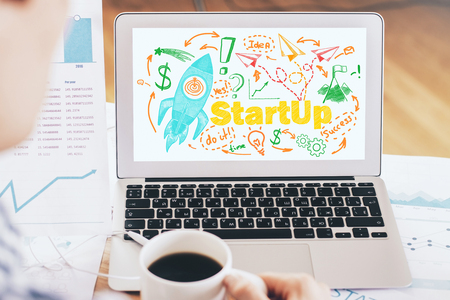 online business: Start up concept with businessman drinking coffe and looking at laptop screen with rocket ship sketch
