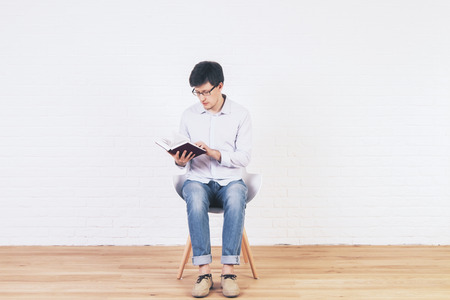 stool test: Caucasian male reading book in empty interior with brick wall and wooden floor
