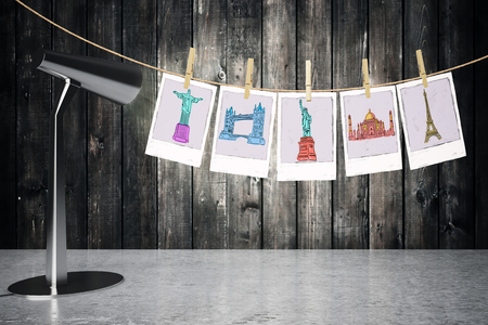 sights: Travel concept with table lamp next to pictures of sights hanging on a rope with pegs on wooden plank background