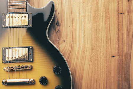funk: Closeup of black and yellow electric guitar on natural wooden surface