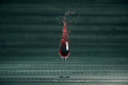 winery: Splashing glass of wine on dark grey background. 3D Rendering