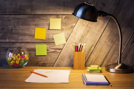 front office: Closeup of creative designer desktop with lamp, crumpled paper in glass bowl and stationery items on wooden wall background