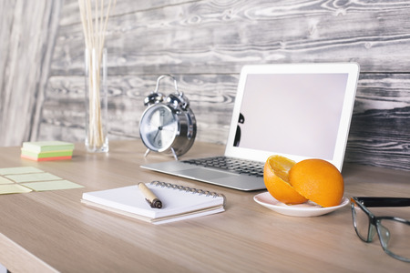 other side of: Side view of creative designer desktop with blank laptop screen, orange slices on saucer, silver alarm clock and other items on wooden background. Mock up