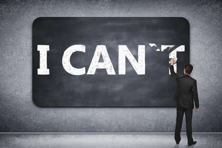 i t: I can, self motivation concept. Businessman wiping letter T off chalkboard in concrete room so that it reads i can
