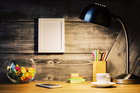 stationery items: Creative hipster desktop with lit lamp, picture frame, coffee cup, smart phone and stationery items. Mock up